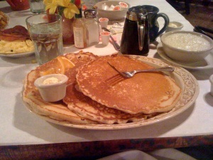 A stack of three plate-sized pancakes.